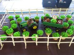 John Deere cupcake display featuring a tractor, wagon, and fencing.  See more John Deere birthday party ideas at www.one-stop-party-ideas.com