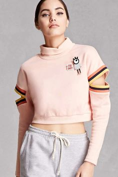 "A French terry crop top sweatshirt featuring ""Friday!"" and eye pins, striped trim, long sleeves with cutout, a turtleneck, ribbed trim. This is an independent brand and not a Forever 21 branded item."
