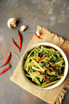 Cook one of the most popular Thai dishes at home with this tasty stir-fry morning glory (water spinach recipe.) It's super quick and vegan-friendly. #thaifoodrecipes #vegetarianrecipes #veganrecipes #quickandeasy