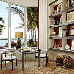 A reading corner gets a sexy edge with modern furniture, a graphic-patterned sisal rug, and an unbeatable view - Traditional Home® / Design: Joseph Pubillones