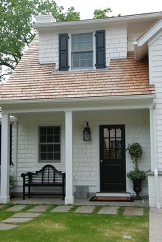 white cedar shake siding (could you use vinyl?) and black door for pool house.