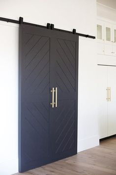 Chic kitchen features a walk-in pantry finished with black chevron sliding doors…