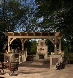 beautiful, casual, outdoor kitchen with elements like these: wood-fire oven, grill, seating, maybe an icebox.