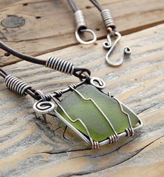This lovely olive coloured sea glass has been uniquely wire wrapped in a rustic and earthy style. The pendant hangs from a waxed cotton brown cord