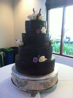 Wedding cake covered in chocolate ganache, decorated with violet and pink roses