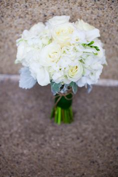 hydrangea, rose and calla lily bouquet wrapped with ti leaves and accented with dusty miller and twine