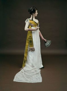 American Federal Dress. India Mull, cut with high waist, open neck gathered on tape, short sleeves and train, embroidered with white cotton in satin stitch and drawn work with undulating band of open work, and sprays of foliage and flowers, up center front of skirt, similar design with open work swags borders skirt, edged with scallops and zig-zag band. Circa 1800.