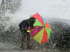 Boy protects himself from wave of a Monsoon in India