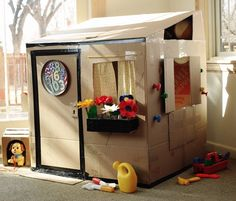 Cool idea for a DIY cardboard playhouse ideas for kids with details like a planter, a real doorknob, a cardboard mailbox. It doesn't have to be perfect to build imagination. via Rust & Sunshin