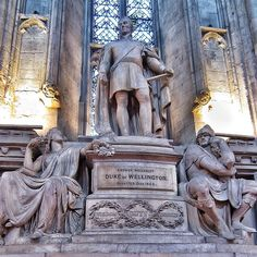 Sculpture in the City of London's Guildhall of Arthur Wellesley, Duke of Wellington with an armed figure on the right below, and a robed figure with a wreath below on the left. All are set on a plinth with a panel showing the charge at Waterloo.