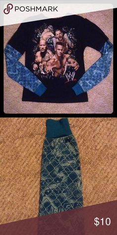 WWE long sleeve shirt Official WWE licensed product. Features WWE superstars Sin Cara, CM Punk, The Rock, and John Cena. Sleeves are dark turquoise with a cage/fence design pattern with the trademark 'W' symbol and 'RAW'. WWE Shirts & Tops Tees - Long Sleeve