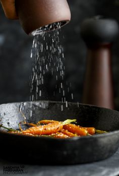 Ground Salt falling from OXO Lily Mills onto Honey Glazed Carrots