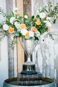 flower arrangement in a silver trophy, photo by Lora Grady Photography http://ruffledblog.com/bowties-and-bourbon-southern-wedding-inspiration #weddingideas #centerpieces #flowers