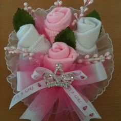 Baby shower roses corsage made with baby socks ,with lace , leaves with a tulle , and satin beautiful bow, pink and white with a small princess crown. Corsage has a diameter of about 6 inches.