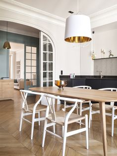 Parisian Kitchen with wood dining table, white wishbone chairs, herringbone wood floors. Wander around this fun and relaxed family apartment in Paris's arrondissement, which balances color with class. Dining Area, Dining Chairs, Dining Table, Outdoor Dining, Parisian Kitchen, Herringbone Wood Floor, Cabinet D Architecture, Moldings And Trim, Crown Molding
