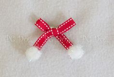 """This beautiful hair bow has red ribbon, with cute white pom poms on the bottom of each ribbon tail. It measures approximately 2"""" by 2', and attaches to the hair with an alligator clip."""