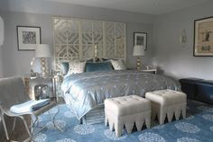 source: Mabley Handler  Glam blue bedroom with Madeline Weinrib Atelier Light Blue mandala Rug, ivory mirrored quatrefoil pattern floor screen used as headboard, mirrored table nightstands with gold trim, champagne metal lamps, light gray tufted ottomans and gray blue walls paint color.