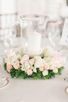 Pastel wedding centerpiece idea - low hurricane vases + white pillar candles decorated with pastel cream + pink flower wreaths {Elizabeth Fogarty}