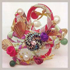 Brazalete con perlas, broches y cintas.