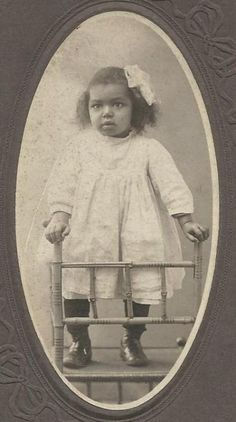 This post cabinet card era photograph features a young chubby cheeked African American little girl. She is adorable and is balancing herself as she stands on a chair. She is wearing a hair bow and high button shoes. The identity of this cute child and the photographer of this image are unknown.