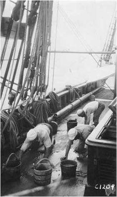 Men holystoning deck.
