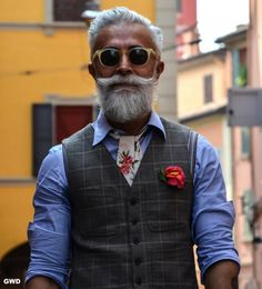 Charcoal tartan vest over sky dress shirt w/ floral on white necktie & matching floral pocket decoration, light grey hair & beard, circular eyeshades w/ frames to match mustard bulding beyond