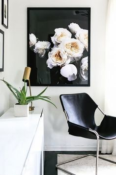 Minimalist living room nook with a black leather armchair, a floral print, and a white storage dresser