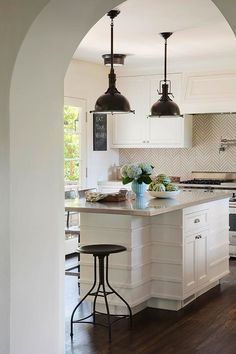 White kitchen cabinets and walls, hardwood floors, herringbone backsplash
