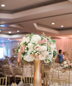 Most popular Wedding Reception centerpiece:  Tall round ball shape centerpiece with gold tall vase and ivory theme color and light pink roses plus some green leaves.