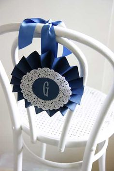 Pretty paper rosettes, tied to the back of the guests chairs and stamped with their initials adds a personal touch and helps guests find their seats more easily at a #wedding. Visit http://modernweddingblog.com/2012/04/05/chair-cover-alternatives to find out more about alternative chair covers.