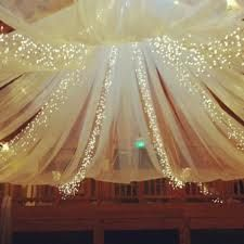 Tulle and twinkle lights. Could be cheap if you bought the tulle in bulk, and the lights on line. Plus if you put it on a hula hop to the center of the reception hall, hand a chandelier in the middle! Would be beautiful!