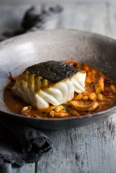 Skrei is a delicious Norwegian cod with a wonderful flaky texture. In this easy recipe, pan-fried skrei fillets are served with buttery cannellini beans and tender braised squid