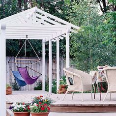 Pergola with comfortable chairs that hang from the rafters, providing both a fun and relaxing retreat.