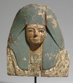 """AN EGYPTIAN PAINTED WOOD COFFIN BOARD. RAMESSIDE PERIOD, DYNASTY XIX-XX, 1307-1070 B.C. The face with hieroglyphic brows and eyes featuring large black irises, wearing a blue wig and broad collar with red, blue, and yellow beads including mandrake fruits and lilies. 19 in. (48.2 cm) high "" ^**^ allison brooks janney ^**^"