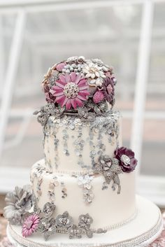Bejeweled cake, we coordinated our cake topper to go with our beautiful jeweled bouquet. We even do centerpieces too! See more here: https://couturejewelrybouquets.com/portfolio-items/cake-decor-2/