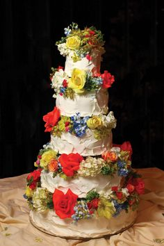 A white cake with bold, colorful flowers makes a summery statement at any wedding