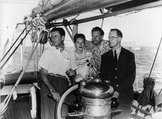 Errol Flynn, his wife Nora, and his father (the man in glasses) sailing with their Siamese cat
