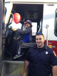 """Zachy """"driving"""" fire engine with Firefighter looking on."""