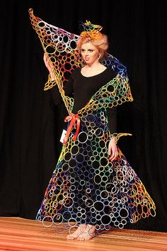 "From Diana Eaton's FB post on November 14, 2014:  ""Made from 1000s of plastic tamperproof rings from milk bottles, Vegemite jars, yoghurt and pet food containers. All held together by fishing line. The most expensive part of this dress was the boxes of bandaids I used for all the blisters I got from tying all those knots!"""