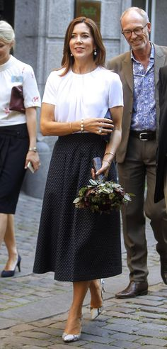 Crown Princess Mary looked as stylish as ever, in a chic white blouse teamed with a navy polka dot midi skirt.  She finished off her sophisticated ensemble with a pair of snakeskin pumps, adding pearl earrings and a matching bracelet, as she stepped out to opened the new center in Copenhagen.
