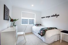 Single bedroom with white desk and black typography wall art.   #ourstories #clientreferences #bedroom #typographyart #interiordesign #newhome #house #styling #generationhomesnz