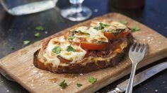 Ringla lite olivolja på brödet. Lägg på prosciutto, tomat och toppa med mozzarella. Lägg mackorna på en plåt med bakplåtspapper och sätt in i ugnen 6-7 minuter till de fått fin färg.