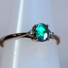 Gorgeous fiery rolling flash 4.5 out of 5 bright green & blue colouring with lots of color movement from this N2 dark solid Lightning Ridge opal. Perfectly cut, this gem is set into a solid 18ct white gold 4 prong basket setting with two .01ctw HI color VS quality brilliant cut diamonds set to highlight. This wonderful solid opal measures 5.70mm X 4.40mm and the beautiful ring is currently size US 6 , UK & AU size M, but for the lucky new owner we can size to fit for you free of charg...