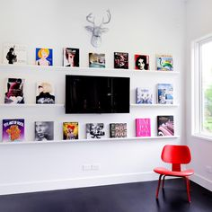 A collection of pop art books cleverly becomes a gallery wall. The bright color theme is picked up in the cherry red chair. Shelf Above Tv, Book Storage, Storage Ideas, Kitchen Storage, Storage Solutions, Wall Bookshelves, Bookcases, Book Wall, Modern Victorian