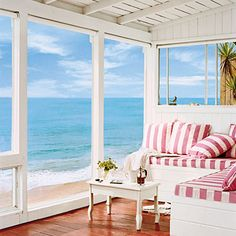 Pink striped cushions contrast the blue of the ocean in this cozy beachside space