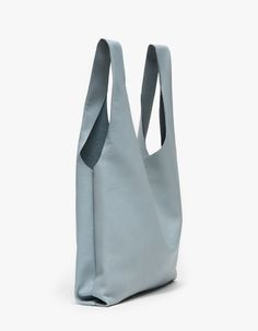 Textured leather classic tote style bag from BAGGU in Smokey Blue. Features two top handles and a simple shape made of the softest natural milled leather. • Textured leather blue tote • Casual, slouchy style • Soft shape • Unlined • 100% Leather •