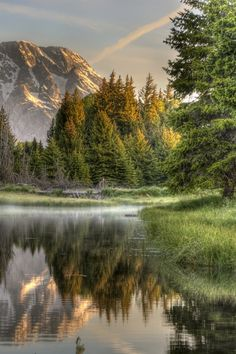 An alpine lake at sunrise. Trees reflect their warm colors in the calm water of a mountain lake.