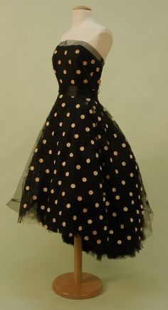 "LANVIN CASTILLO, PARIS, DOTTED TULLE STRAPLESS DRESS, c 1950. Black silk with boned bodice and full layered skirt dotted in bone velveteen, back cut to reveal a ruffled tulle bustle effect on underskirt with many layered tulle hem ruffle, silk satin waistband and braided back bow detail, side zipper, skirt back closes to hem with hooks & eyes. Labels ""Jeanne Lavin Paris"" and ""Castillo""."