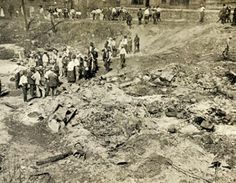 """East St. Louis """"Race Riots,"""" 1917  Police and others look for bodies after the riot in East St. Louis. Local investigations were inept, making accurate an death count improbable. The bodies of some black victims were buried in a common grave. Others were thrown into Cahokia Creek, which ran between downtown and the riverfront railyards.  Photo credit: Southern Illinois University Edwardsville, Bowen Archives"""