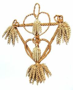 This corn dolly was made by Alec Coker. It consists of a spirally-woven triangular frame with bunches of corn ears at each point. Within the triangle are two heart-shaped plaits joined and decorated with plaited circles and bunches of corn ears. (MERL/86/178)